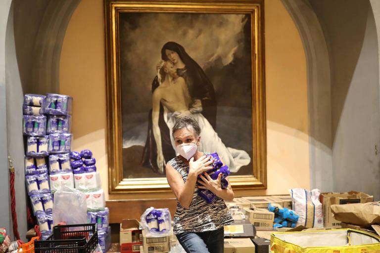 Uma mulher, com cabelos curtos e grisalhos, segura nos braços pacotes azuis. Atrás dela há um quadro de Maria com o Jesus no colo, após a crucificação