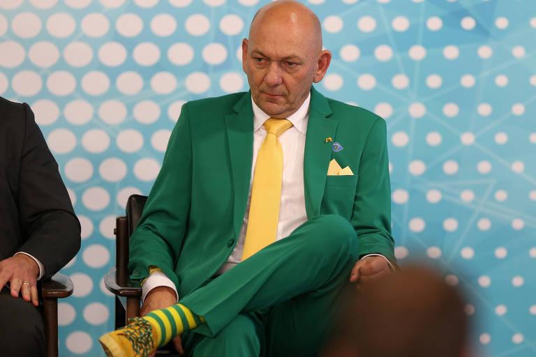 Hang, um homem branco, careca e que veste terno verde, com gravata amarela, sapato amarelo e meias listradas em verde e amarelo. Ele está sentado e com a perna cruzada