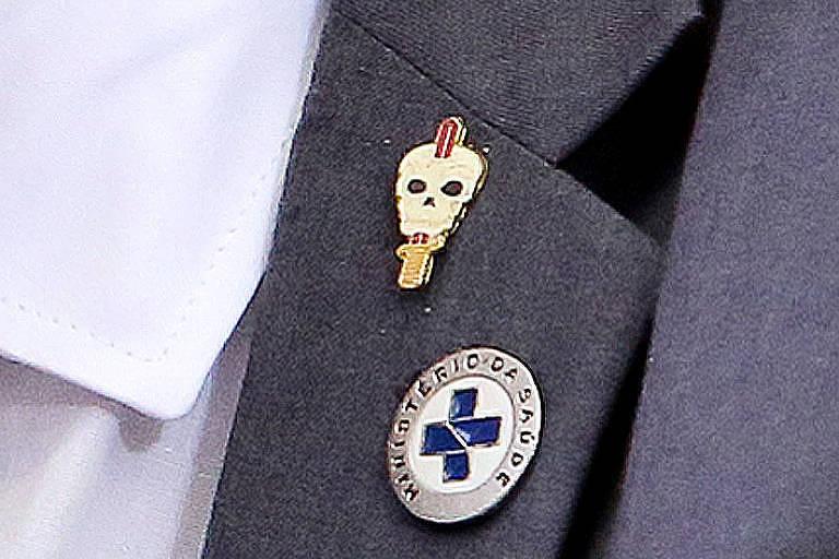 Broche do Comando de Operações Especiais --com uma faca enfiada o crânio de uma caveira--, ao lado do símbolo do Ministério da Saúde, na lapela de Elcio Franco em entrevista coletiva no dia 25 de maio
