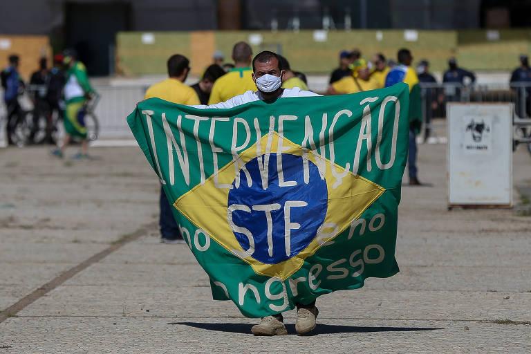 Manifestante mostra bandeira do Brasil na qual se lê: intervenção no STF e no Congresso