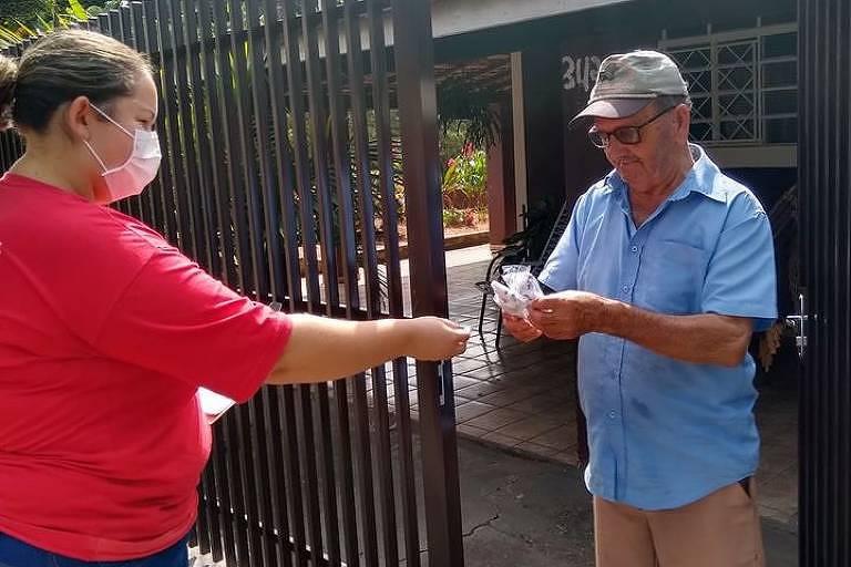 Funcionária da Secretaria da Saúde de Cafelândia distribui máscaras a morador da cidade