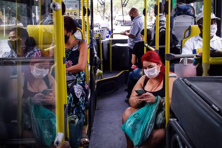 Passageira de máscara senta no degrau do ônibus na linha Jardim dos Cunhas, em São Paulo