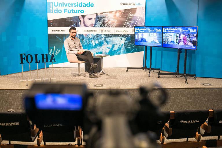 Fabio Takahashi aparece sentado em um palco, na frente do banner do seminário; ao seu lado, dois monitores mostram os convidados que acompanham o evento online