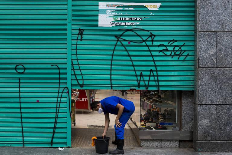 Homem limpa fachada de loja em São Paulo; apesar do Pronampe, pequenos comerciantes sem relação prévia com bancos tiveram dificuldade para acessar crédito