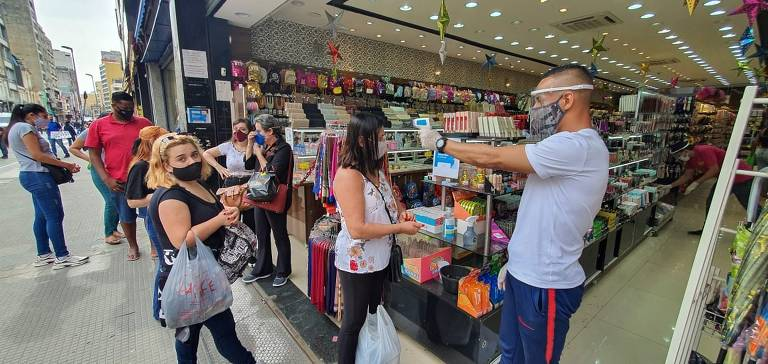 Clientes fazem fila à espera da reabertura das lojas na região da rua 25 de março