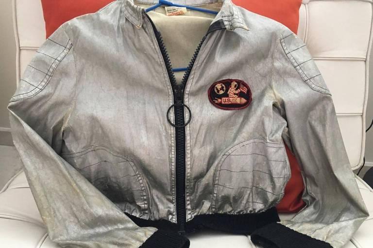 Foto da jaqueta prateada vintage em cima de uma poltrona branca