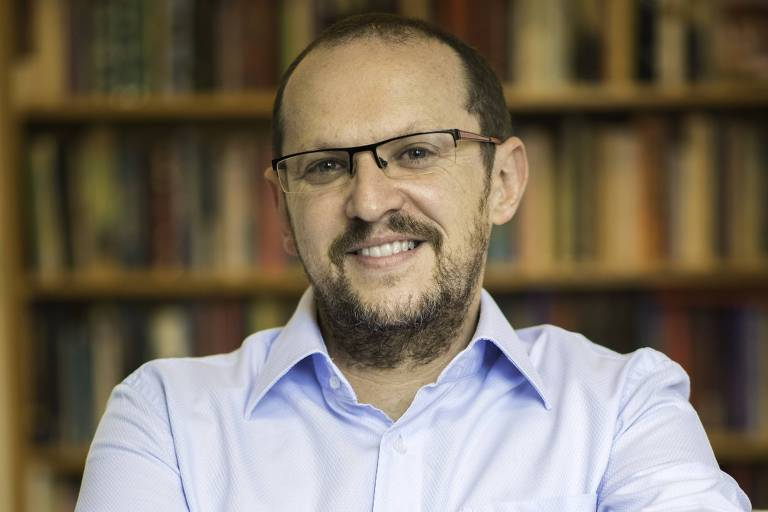 Escritor calvo, veste camisa azul e usa óculos. Ele está sentando em uma poltrona de perna cruzada e sorri para a foto
