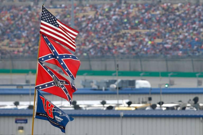 No topo, a bandeira dos EUA e, logo abaixo, duas bandeiras confederadas, símbolo hasteado há décadas pela Nascar e banido em 2020 por sua associação à escravidão