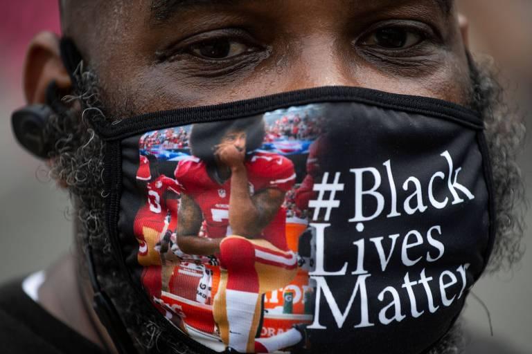 Homem negro com máscara em que o jogador de futebol americano aparece agachado no hino nacional e a #blacklivesmatter