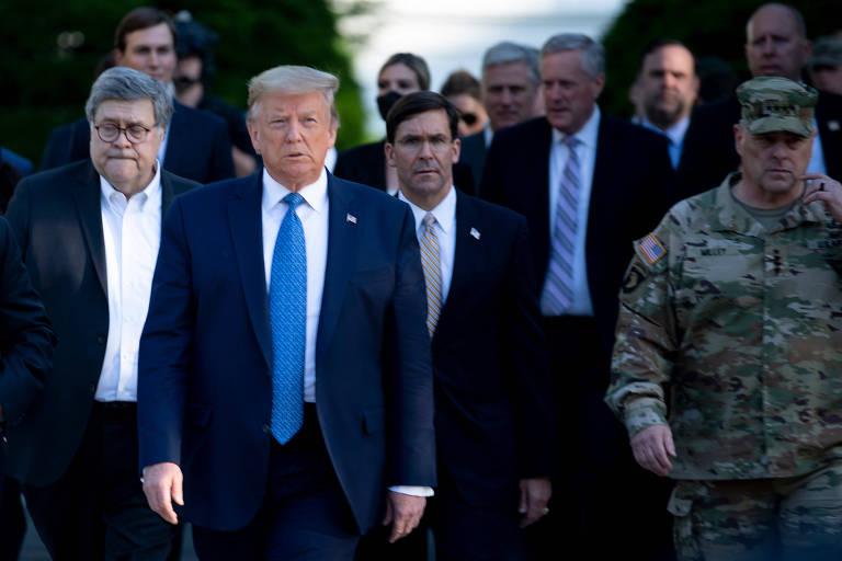 O presidente Donald Trump, à frente, de gravata azul, caminha junto com Mark A. Milley, de uniforme militar, à dir., em direção à igreja de St. John, em Washington