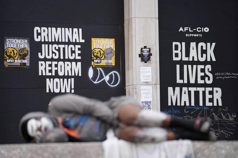 Homem dorme em banco em frente a cartazes do movimento 'Black Lives Matter' próximos à Casa Branca