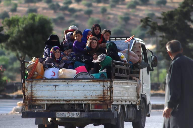 Em caçamba de caminhão, sírios fogem em rodovia em Ariha, na província rebelde de Idlib