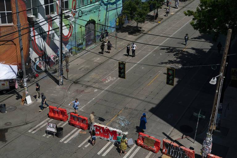 imagem da esquina de uma rua, vista de cima, apenas algumas pessoas andam pela faixa de pedestres e pela rua. há proteções de trânsito laranja sobre a faixa de pedestres