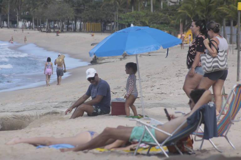 Turistas estendidos na areia da praia, no litoral norte de SP