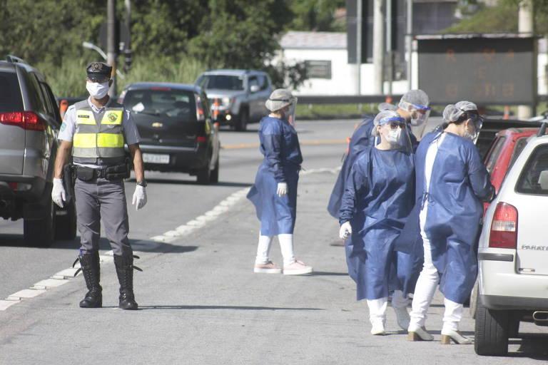 Agentes da polícia estão no meio de uma rodovia organizando o fluxo de carro e agentes da vigilância sanitária, usando roupas azuis e máscaras, medem temperatura de motoristas