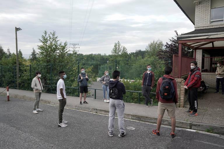Estudantes da escola Axular Lizeoa esperam na calçada portão abrir, respeitando distanciamento social