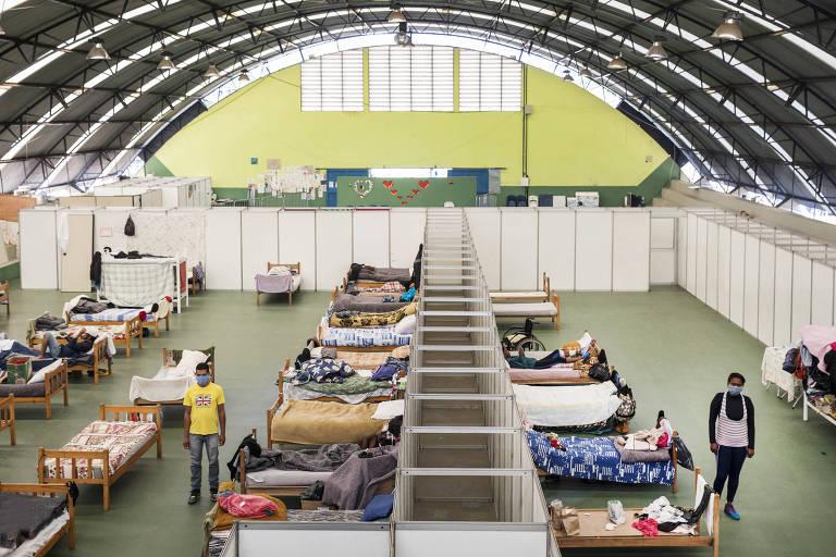 No ginásio, o casal tem que dormir em alojamentos separados (masculino e feminino), pois quarto para namorados do abrigo esta ocupado por morador em quarentena; vemos a estrutura do ginásio fotografada do alto, de modo que se veem as camas e a divisão entre os alojamentos