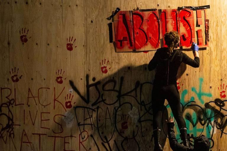 Manifestantes picham parte externa do departamento de polícia de Seattle com a palavra 'abolir', pedido de ativistas para acabar com a polícia