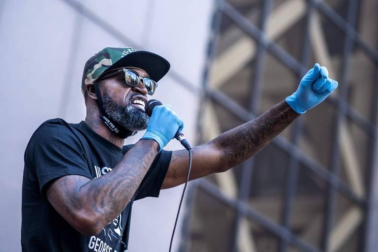 Stephen Jackson, com luvas azuis nas mãos, empunha um microfone e gesticula enquanto fala