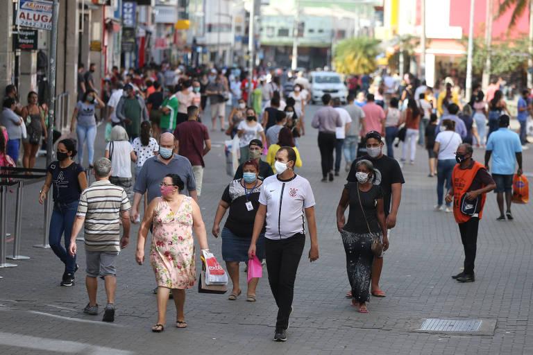 Pessoas andam rua de comércio em Guarulhos