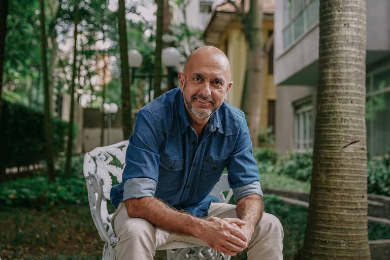 José Roberto sentado em cadeira em área comum de um prédio, com árvores ao fundo