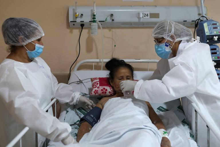 Mulher da etnia mura recebe atendimento no hospital estadual Nilton Lins, em Manaus; vemos um leito de hospital, de ferro, com uma mulher que recebe água de um profissional de saúde; do outro lado do leito, outra profissional observa