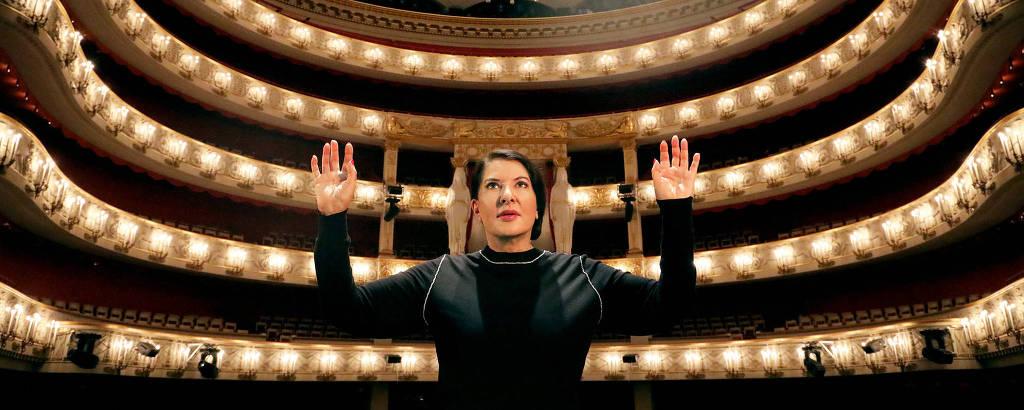 mulher rege orquestra fictícia em ópera