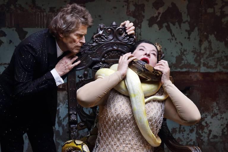 mulher é asfixiada por cobra enquanto homem a observa