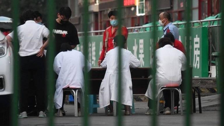 Vistas por entre barras, pessoas são testadas para coronavírus