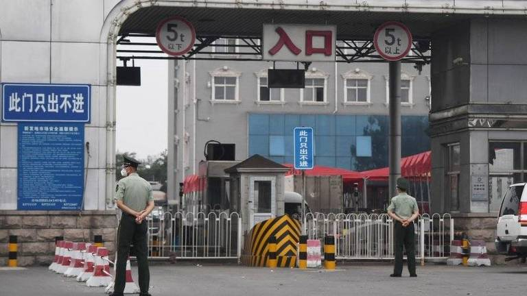 Dois guardas de costas em frente a portão