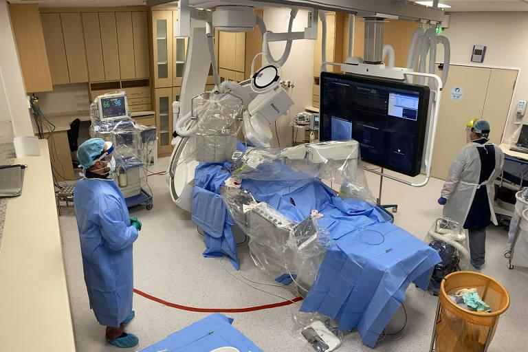 Pessoas paramentadas como médicos e enfermeiros observam cama hospitalar vazia envolta em plástico e rodeada de aparelhos