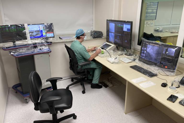 Homem paramentado como médico trabalha diante de computador em sala envidraçada