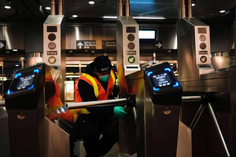 Funcionário do metrô de Nova York limpa catracas em estação para tentar diminuir contaminação por coronavírus