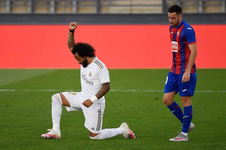 Na imagem, o zagueiro brasileiro do Real Madrid Marcelo se ajoelha no meio do campo e ergue um dos braços com o punho cerrado. Atrás dele, há outro jogador em pé.