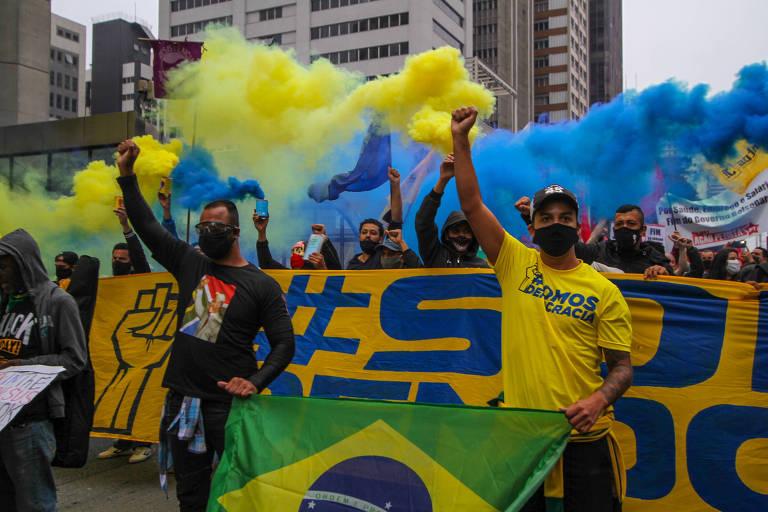 Um homem com camiseta e outro com amarela em frente a uma faixa amarela com dizeres em azul. Atrás dela, manifestantes soltando fumaça na cor amarela e azul. Todos com o braço direito erguido
