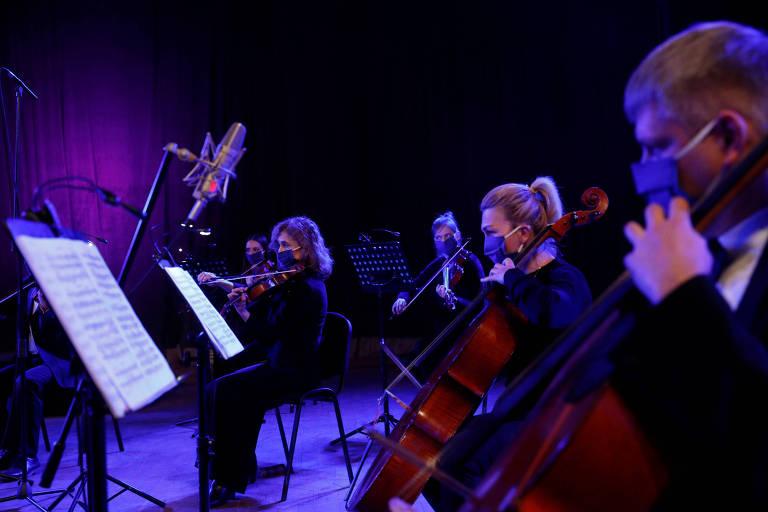 sob luz azul, uma mulher e um homem tocam violoncelo, ao fundo, três mulheres tocam violino. todos usam máscaras