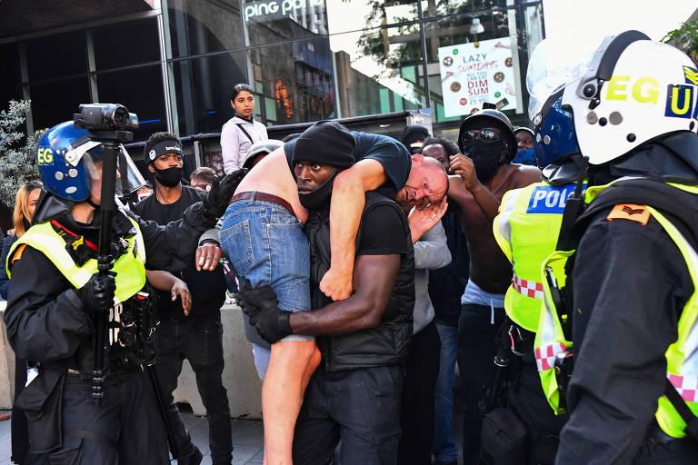 O ativista Patrick Hutchinson carrega um homem branco ferido próximo à estação Waterloo durante protesto em Londres