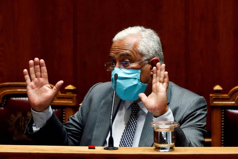 António Costa, com máscara azul clara e terno cinza, está sentado em uma das cadeiras do parlamento, em frente a um microfone e um copo d'água. ele gesticula enquanto fala, mostrando as palmas da mão