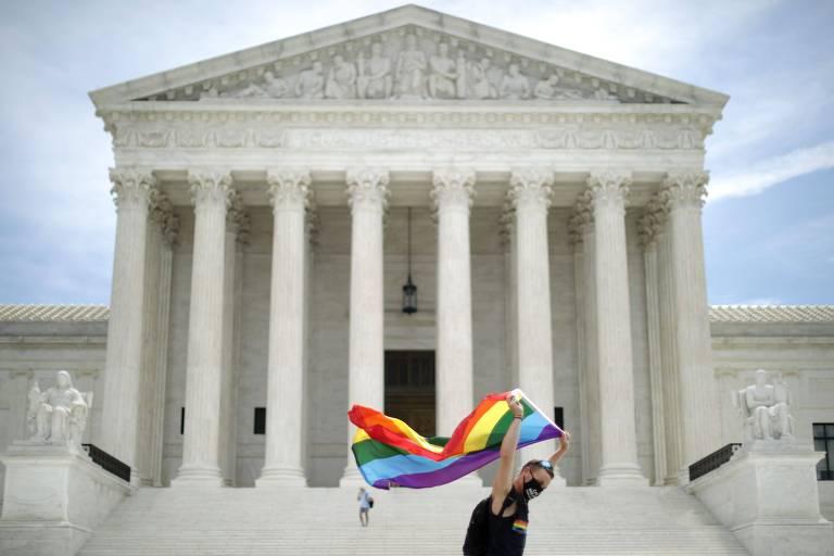 Ativista com bandeira símbolo da comunidade LGBT em frente à Suprema Corte americana, em Washington
