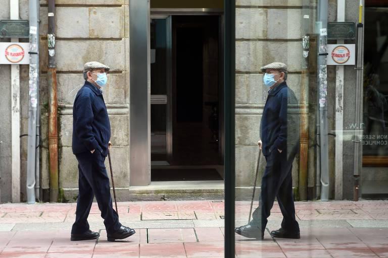Um idoso, com uma bengala, de casaco e calças pretas e com uma boina bege caminha em uma calçada. A imagem dele está refletida em um vidro que está à sua direita. a impressão é de que ele está caminhando em direção a ele mesmo