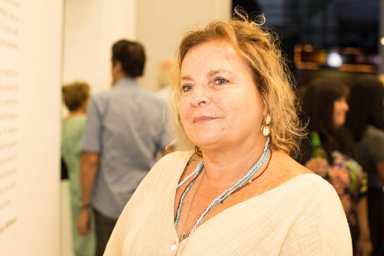 Mulher loira de olhos claros, branca, vestida de maneira elegante. Ela está em uma galeria de arte, com intensa luz amarela, e olha para o lado