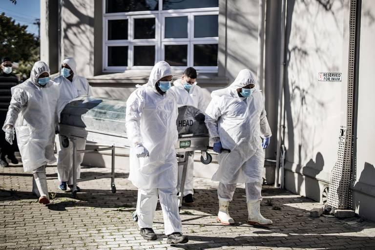 Quatro pessoas com uniformes de proteção brancos empurram carrinho com caixão na Cidade do Cabo, na África do Sul, em junho