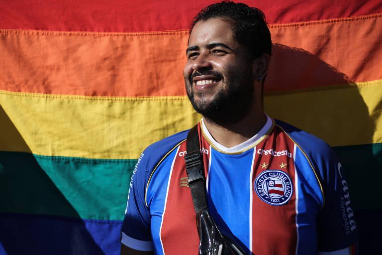 Onã Rudá posa com camisa do Bahia em frente a bandeira LGBT
