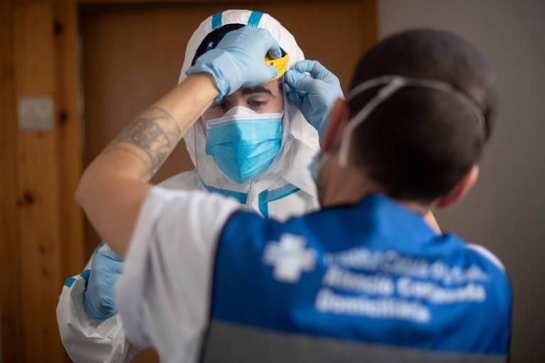 Membro da equipe de apoio técnico auxilia profissional de saúde a colocar equipamento de proteção em Barcelona