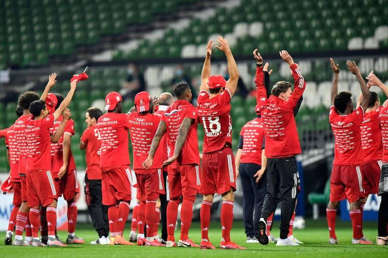 Com camisas comemorativas, mas sem torcedores para saudar, jogadores do Bayern de Munique celebram no gramado a conquista do octacampeonato consecutivo