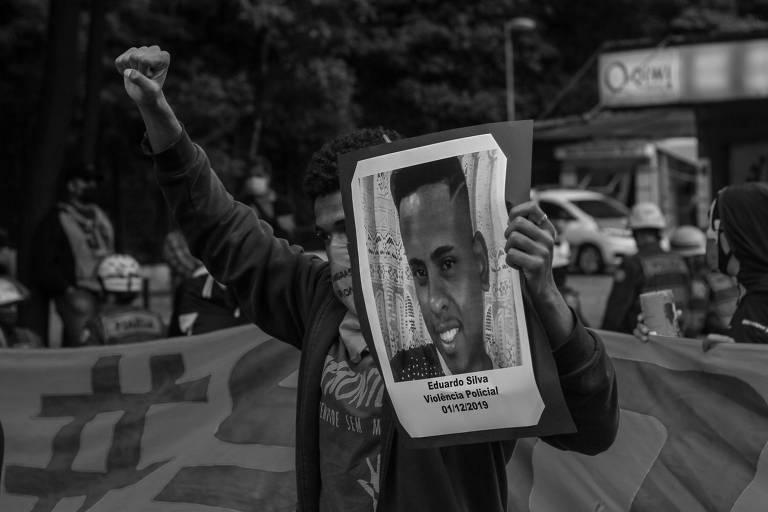 Manifestação conta a violência policial em São Paulo. Na foto, jovem negro segura uma placa com a foto de Eduardo Silva, um jovem morto pela polícia em 2019  (16.jun.2019)