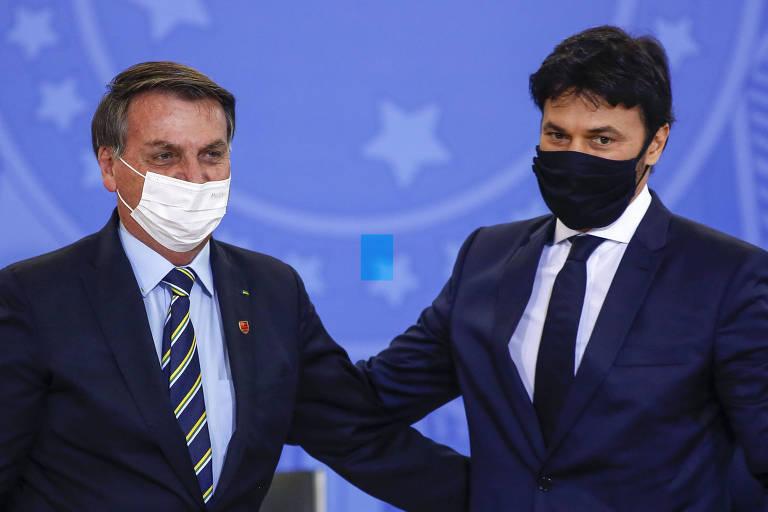 De frente, Bolsonaro coloca as mãos nas costas de Faria, que retribui o gesto