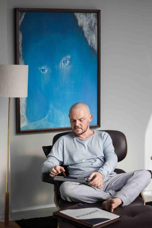 homem careca sentado em cadeira vestindo moletom azul e cinza