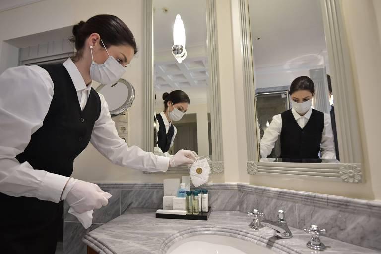 Mulher com uniforme de camareira coloca máscara descartável em pia de banheiro