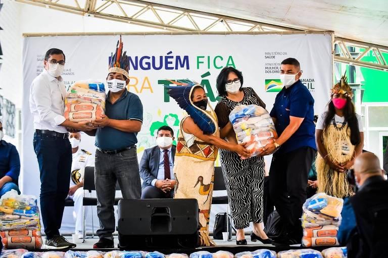 Damares Alves em entrega simbólica de cestas básicas a indígenas do Amazonas; sobre um palco, há seis pessoas, três trajando cocares, Damares e dois outros homens, que devem ser da Companhia Nacional de Abastecimento em Manaus, onde ocorreu a entrega; a ministra e uma das indígenas segura um pacote de víveres, ajudadas por um dos homens